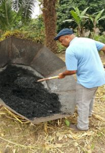 Mr. Ivo Tasong - secretary of FESCAM - recovering the first biochar produced by FESCAM Coop in Cameroon