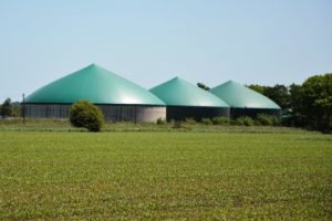 Three biogas production silos near a field.