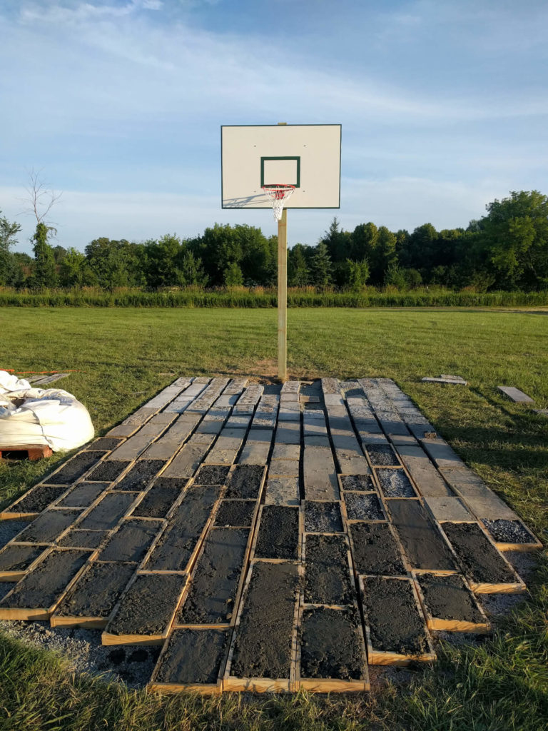Concrete bricks of the basketball court drying in the sun.