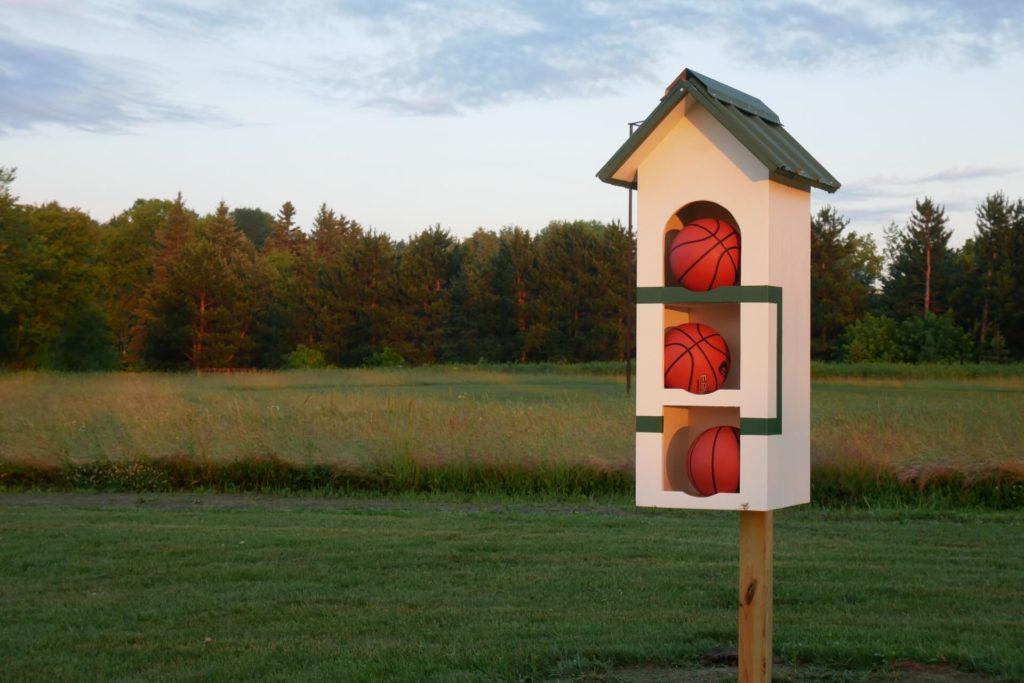 Basketballs stored in a custom birdhouse.