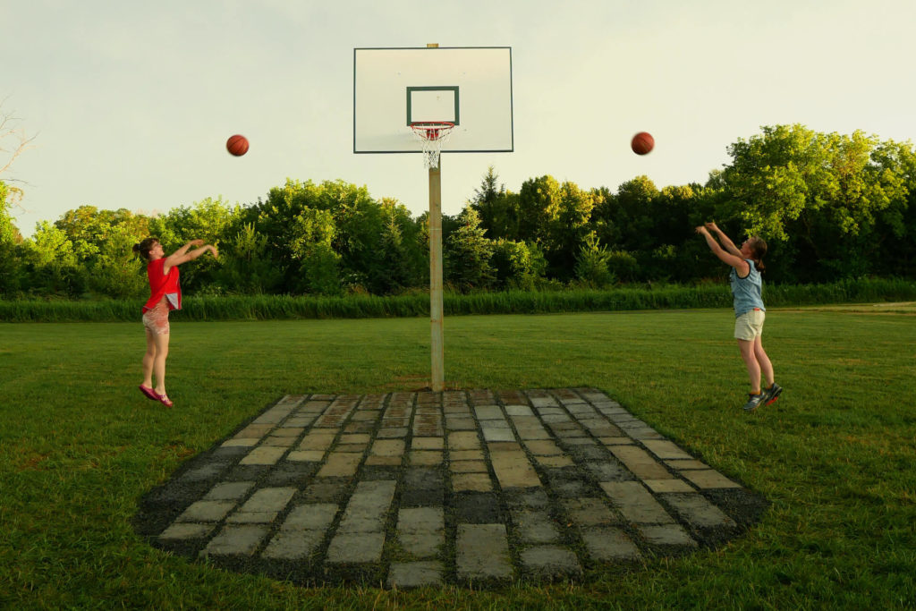 two players jumping and shooting basketballs at the same time in the dirtball installation.