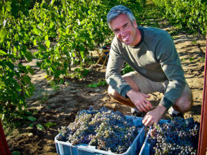 Sandor Johnson with bushels of grapes from his vineyard