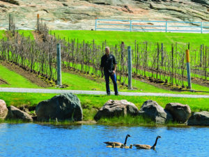 Sandor Johnson next to the water on his vineyard