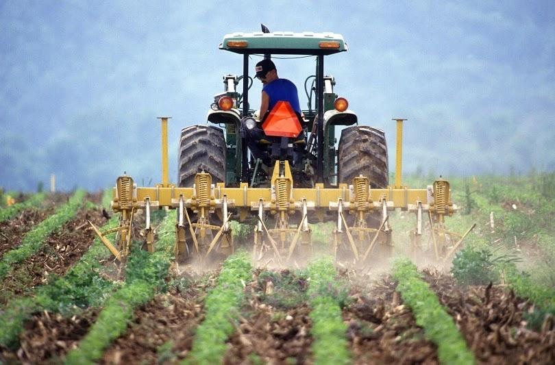 Tractor applying rock dust to a field