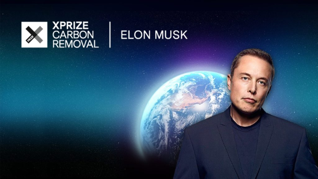 Elon Musk posing in front of a photo of the Earth and the XPrize logo